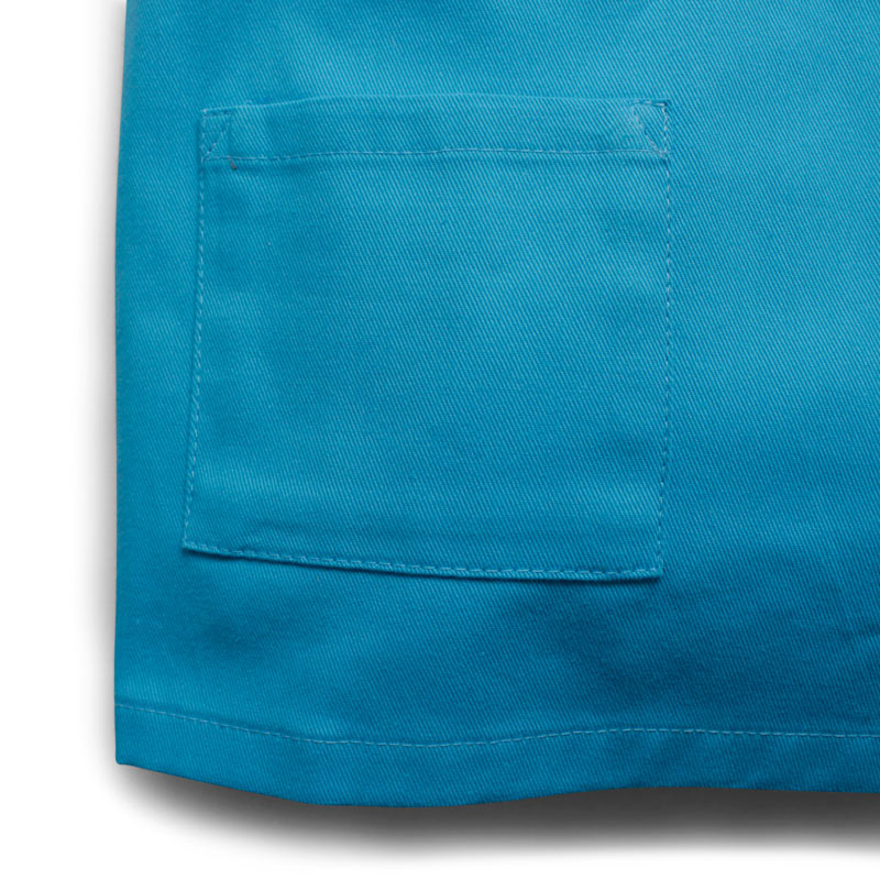 up close detail of children's blue medical scrubs showing the front pocket detail and the cotton twill fabric